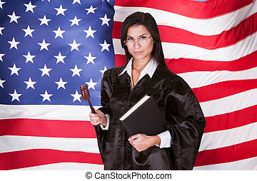 Female Judge With A Law Book And A Wooden Gavel Standing In...