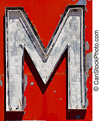 "Vintage, run-down, antique letter ""M"" on a red background"