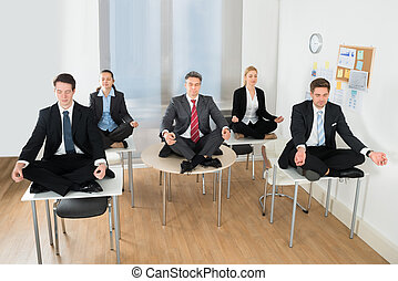 Meditating Businesspeople Sitting On Desk With Their Legs...