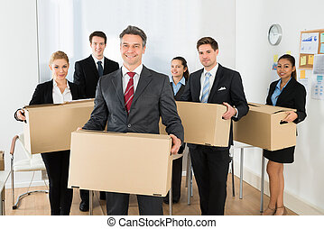 Employees In Office Holding Cardboard Boxes - Portrait Of...