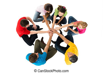 Friends Sitting In A Circle Stacking Hands - Group Of...