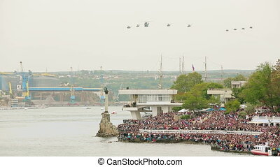 Helicopters flying in the sky during military parade. Overall shot.