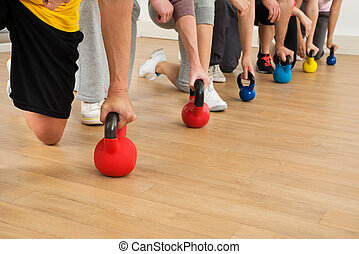 People Holding Colorful Kettle Bell - Close-up Of People...