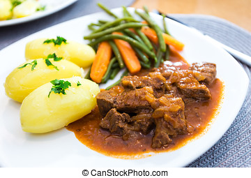 Plate of goulash with potatoes, french beans and carrots.