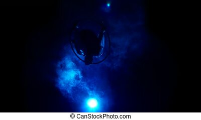 Aerial acrobat man on circus stage. Silhouette on a blue...