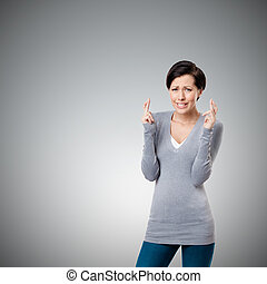 Worried woman shows crossed fingers - Worrid woman shows...