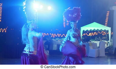 two girsl in red theatrical costume dancing