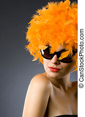 pretty woman wearing an orange feather wig and sunglasses -...