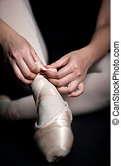 Ballet Slippers - Close up of a ballerina tying her ballet...
