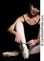 Ballerina Tying Shoes - A young asian ballerina tying her...