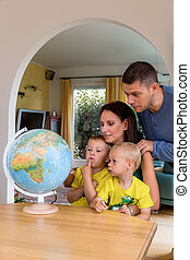 family planning holiday travel - a family sitting on a globe...
