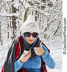 Young positive woman drinking hot tea in winter nature