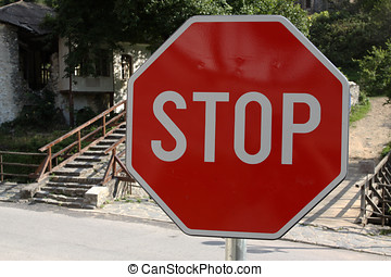 Red stop sign on a stone road