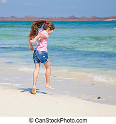little girl with long brown hair in ponytail in pink t-shirt...