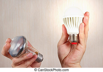 Hands compared incandescent bulb and glowing ecofriendly led lamp on light wood background