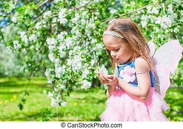 Adorable little girl in blossoming apple tree garden -...