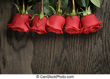 Romantic background with red roses on wood table, top view