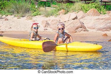 Little adorable girls enjoying kayaking on yellow kayak -...