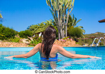 Beautiful young woman relaxing in swimming pool with...
