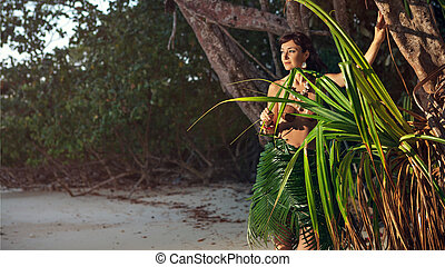 Indigene woman in the palm skirt on the tropical forest...