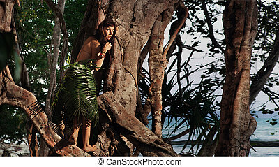 Indigene woman in the palm skirt on the tropical forest and...