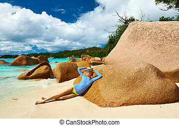Woman at beautiful beach wearing rash guard Seychelles,...