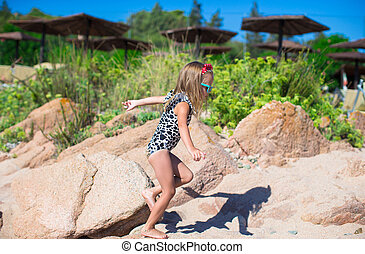 Adorable little girl have fun on white beach during vacation...