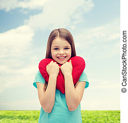 smiling little girl with red heart - love, happiness and...