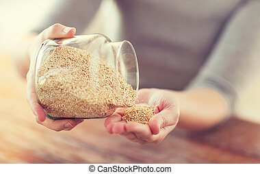 close up of female emptying jar with quinoa - cooking and...
