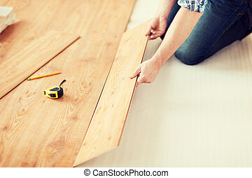 close up of male hands intalling wood flooring - repair,...