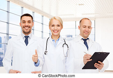 group of doctors showing thumbs up in clinic - healthcare,...