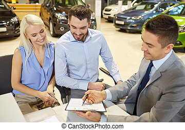 happy couple with car dealer in auto s