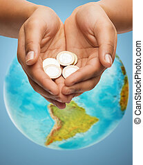 cupped hands holding euro coins over earth globe - money,...