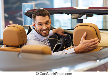 happy man sitting in car at auto show or salon - auto...