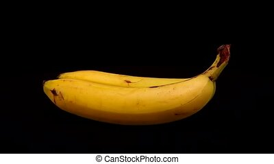 Two bananas are spinning on a black background