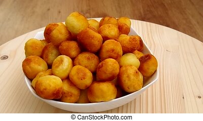Frying potato croquettes rotate on the table
