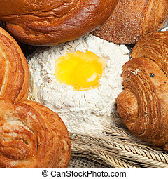 fresh bread with ears of rye and flour background