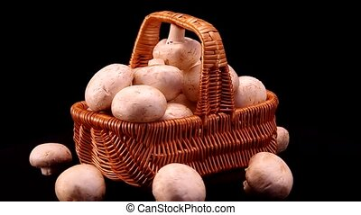 Champignons in a basket on a black
