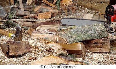 Chainsaw cutting wood in the yard of the house
