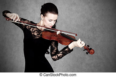 Portrait of a young attractive violinist woman in a black evenin