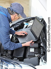 Car Mechanic with diagnostic notebook on car - A Car...