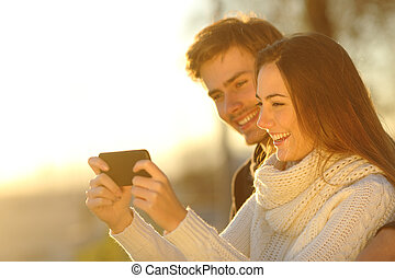 Couple watching media videos in a smart phone - Happy couple...