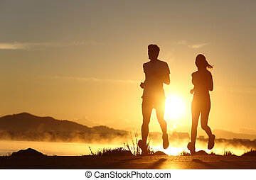 Silhouette of a couple running at sunset with the sun in the...
