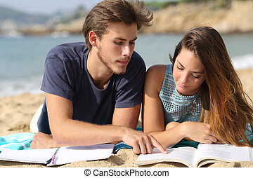 Teenager couple or friends students studying on the beach...
