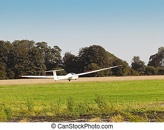 glider landing - a glider landing near a field with trees...