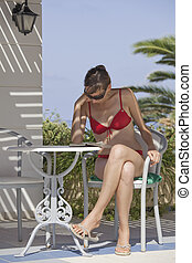 woman in sunglasses reading book on vacation