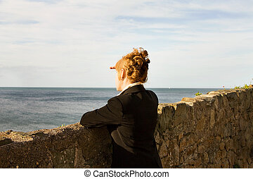 Woman looking at the sea - Irish woman with red hair looking...