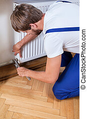 Handyman trying to fix heater - Handyman in blue uniform...