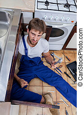 Upset plumber trying to fix the sink - Upset plumber in blue...
