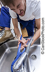 Man trying to repair washbasin tap - Young man trying to...